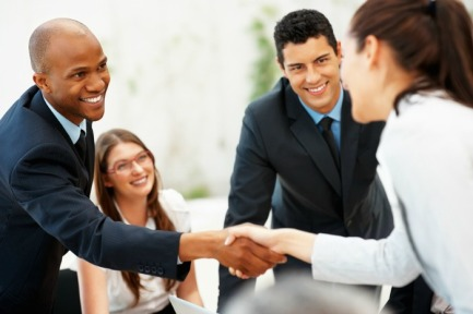 View of executives shaking hands while colleagues smile